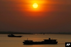 FILE - A dredging river barge, foreground, carries sand in the middle of Mekong River near Phnom Penh, Cambodia, Friday, Jan. 24, 2020. (AP Photo/Heng Sinith)