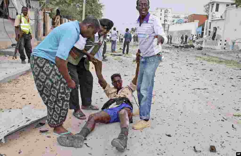 Somali men and a police carry a government soldier wounded during an attack on the U.N. compound in Mogadishu, June 19, 2013.