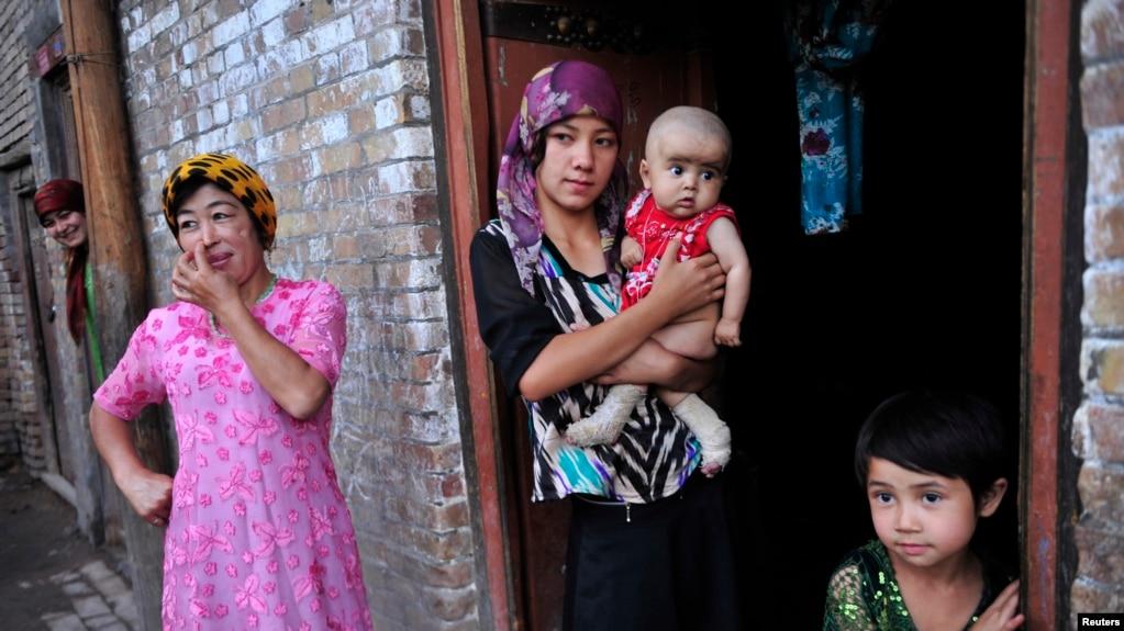 一名维吾尔女子抱着她的儿子站在门口(路透社,2012年7月22日)