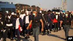 FILE - Italian border police officers escort sub Saharan men on their way to a relocation center, after arriving aboard the Golfo Azzurro rescue vessel at the port of Augusta, in Sicily, Italy.