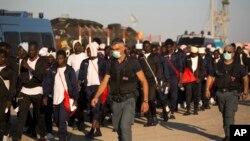 Des policiers de la frontière italienne escortent vers un centre de relocalisation des migrants subsahariens arrivés à bord du navire de sauvetage Golfo Azzurro au port d'Augusta, en Sicile, Italie, 23 juin 2017.