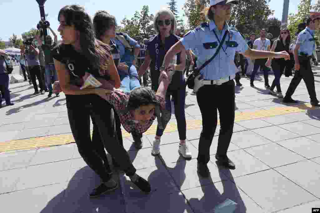 Riot police officers detain protesters during the trial of two Turkish teachers who went on a hunger strike over their dismissal under a government decree following last year's failed coup, outside of a courthouse in Ankara, Turkey.