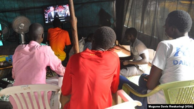 Young men watch sport on a small television in a makeshift viewing hall in UNMISS's Tongping Protection of Civilians site in Juba.
