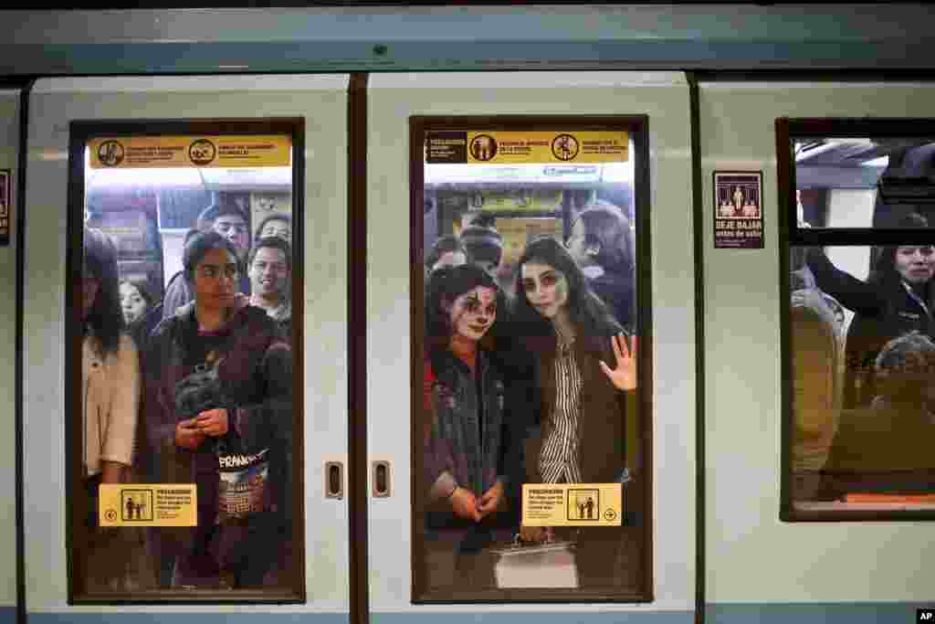 Two young women, with their faces painted for Halloween, travel in the subway in Santiago, Chile, Oct. 30, 2018.