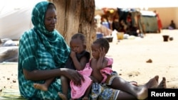 A Malian family displaced by war gather at a makeshift camp in Sevare, about 600 kilometers northeast of the capital Bamako, July 11, 2012.
