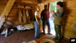 FILE - Ruth Toliner, left, and her husband Lowell Toliner, of Olney, Md., ask Steve Bashore questions about this newly reconstructed slave cabin at George Washington's Mount Vernon estate in Mt. Vernon, Va, Sept. 19, 2007. Scholastic Publishing is recalling one of its children's books from bookstore shelves in the U.S as it may give a false impression of the reality of the lives of slaves.