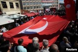 FILE - People carry the Turkish flag as Turkish President Recep Tayyip Erdogan and his Serbian counterpart, Aleksandar Vucic, visit Novi Pazar, Serbia, Oct. 11, 2017.