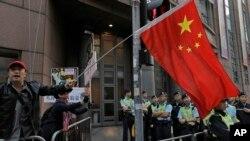 Một người biểu tình ủng hộ Bắc Kinh giương lá quốc kì TQ trong một cuộc tuần hành đầu năm mới tại Hong Kong.