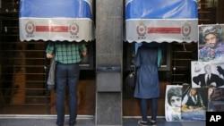 FILE - Iranians use ATM machines of Bank Melli Iran in downtown Tehran, Iran, April 4, 2015.