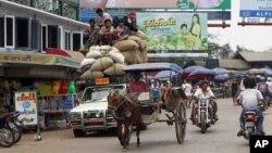 Vehicles make their way on a road near local bazaar in Mawlamyine, Mon State, Burma, March 11, 2011.