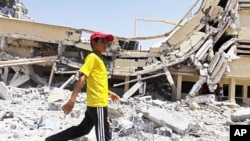 A child walks past the rubble of a university building in Zlitan, Libya, August 4, 2011