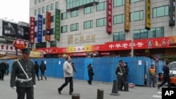 Chinese guards stand at the entrance of the pedestrian Wangfujing area in Beijing. The blue metal barriers are part of a construction site that partially blocks a designated spot for anti-government protests, February 25, 2011.
