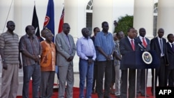 The seven detainees from South Sudan, shown here with Kenyan President Uhuru Kenyatta, after they were released to his custody, will be a third party at peace talks for South Suidan, along with pro- and anti-government negotiators.