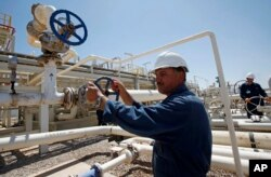 FILE - Employees work at the Tawke oil field in the semiautonomous Kurdish region in northern Iraq, May 31, 2009.