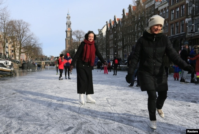 People ice skate during a cold snap across the country at the Prinsengracht in Amsterdam, Netherlands February 14, 2021. (REUTERS/Eva Plevier)
