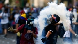 An anti-government protester throws a gas canister at the police during clashes at Altamira Square in Caracas, Venezuela, March 3, 2014.