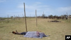 FILE - The lifeless body of a man is covered with a shroud as it lies in an open field in Kismayo, Somalia. Inter-clan violence killed six people Saturday in Labi-Aano village, 45 km east of Dhuusamareeb, Somalia.
