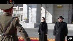 Un militaire salue le leader nord-coréen Kim Jong Un et sa femme Ri Sol Ju, lors d'une parade militaire a Pyongyang, Corée du Nord, le 8 février 2018.