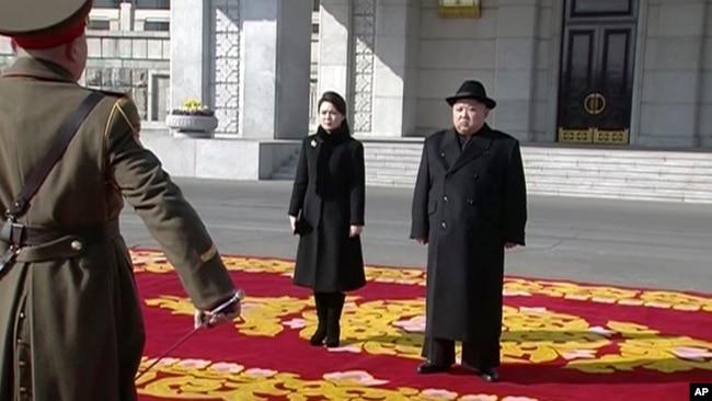 Imagen tomada de la televisión de Kim Jong Un y su esposa, en un desfile militar en Pyongyang.
