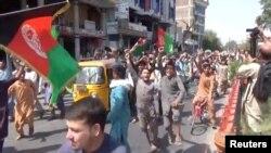 Orang-orang membawa bendera Afghanistan dalam aksi protes anti-Taliban di Jalalabad, Afghanistan, 18 Agustus 2021 dalam tangkapan layar yang diambil dari sebuah video. (Pajhwok Afghan News/Handout via REUTERS)