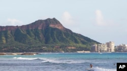FILE - Surfers ride waves off Ala Moana Beach Park in Honolulu, with Diamond Head mountain in the background. Out of sight of tourists are disused military tunnels beneath the crater.