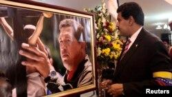 El presidente a cargo Nicolás Maduro observa una fotografía de Hugo Chávez, durante sus funerales.