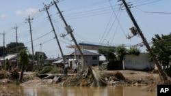 2015年9月11日东京东北部茨呈县常总遭水灾,电线杆被水冲后出现倾斜。
