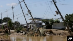 Electric poles tilt damaged after floods hit Joso, Ibaraki prefecture, northeast of Tokyo, Friday, Sept. 11, 2015.