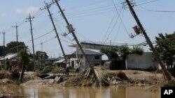Electric poles tilt damaged after floods hit Joso, Ibaraki prefecture, northeast of Tokyo, Friday, Sept. 11, 2015.
