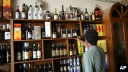 FILE -- A man looks at bottles of alcohol on sale in liquor store in Baghdad, Iraq. Iraq's parliament passed a law forbidding the import, production or selling of alcoholic beverages.