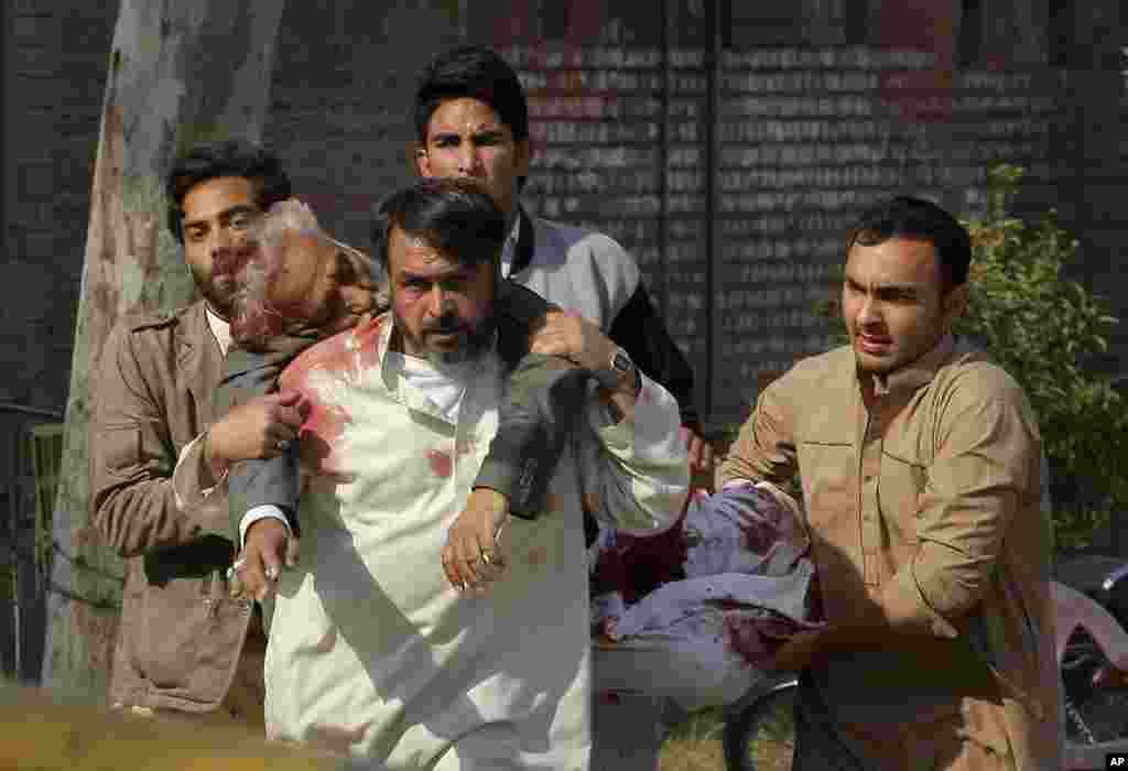 People rush an injured person to a hospital following an attack involving suicide bombers and gunmen at a Shiite mosque in Peshawar, Pakistan.