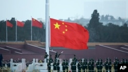 FILE - Chinese paramilitary policemen perform a flag raising ceremony on Tiananmen Square in Beijing, March 5, 2016.