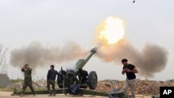 FILE - Iraqi security forces fire at Islamic State militants positions from villages south of the Islamic State group-held city of Mosul, Iraq.