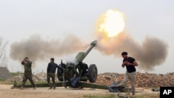 Pasukan keamanan Irak menembakka roket ke arah militan ISIS dari desa di sebelah selatan kota Mosul yang dikuasai ISIS di Irak (26/3).
