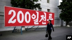 "A North Korean woman walks past a sign which reads ""200-day campaign,"" in Pyongyang, North Korea on Saturday, June 25, 2016."