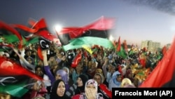 File - In this Sunday Oct. 23, 2011 file photo, Libyan celebrate at Saha Kish Square in Benghazi, Libya.