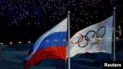 FILE - The Russian national flag flutters next to the Olympics flag during the closing ceremony for the 2014 Sochi Winter Olympics, Feb. 23, 2014.