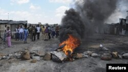 Para pekerja tambang yang mogok membakar ban bekas dan memblokir jalanan di luar pertambangan Anglo American Platinum (Amplats) dekat Rustenburg, 120 kilometer sebelah barat laut Johannesburg (30/10). Polisi Afsel membubarkan mereka dengan menembakkan gas air mata dan peluru karet.
