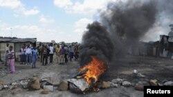 罷工工人在英美鉑業礦場外焚燒雜物阻擋汽車駛入