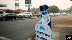 在加州雷丁,一位平时为一家电脑修理店做广告的男士亮出感谢消防队员的标语牌。(2018年8月13日)