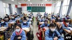 چین میں اسکول کھول دیے گئے ہیں۔ ایک کلاس روم میں بچے تعلیم حاصل کر رہے ہیں۔