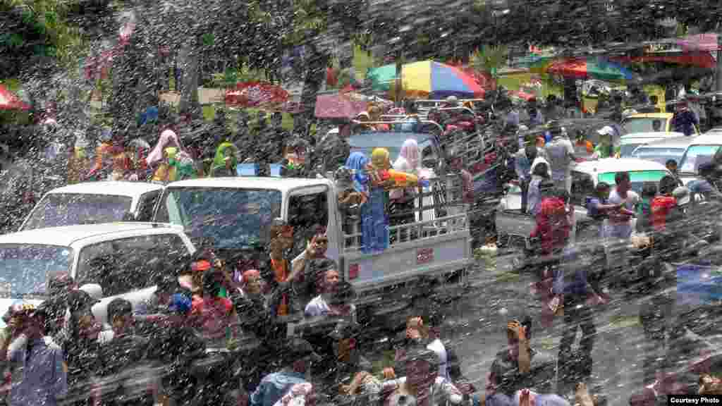 People on a truck react after being splashed with water while others shoot back using water guns during the traditional Burmese water festival on Pyi Road in Rangoon, Burma, April 16, 2014. (MoeMoe Htun/VOA).