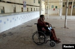 FILE - A patient in a wheelchair waits at a medical center in Karachi, Pakistan, Sept. 17, 2015. No data has been collected on the number of disabled in Pakistan since 1998.
