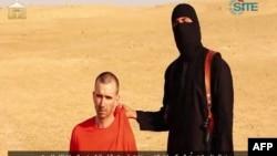 Gambar yang diambil dari video yang dirilis oleh ISIS menunjukkan militan bertopeng mengancam akan membunuh warga Inggris David Cawthorne Haines.