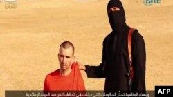 伊斯兰国恐怖主义组织发布的一段视频显示,一名蒙面的武装人员威胁要将英国人大卫·海恩斯斩首。本图为视频截图