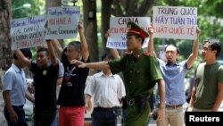 Một nhân viên cảnh sát cố gắng ngăn cản người biểu tình chống Trung Quốc cầm biểu ngữ trong một cuộc biểu tình trước đại sứ quán Philippines tại Hà Nội, Việt Nam, ngày 17/7/2016.
