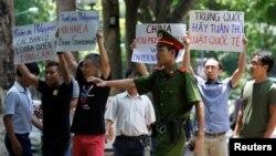 2016年7月17日在越南河内一名警察试图阻止反华抗议人士。