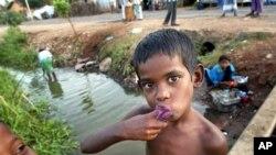 Một bé trai Sri Lanka đánh răng bằng nước từ con kinh