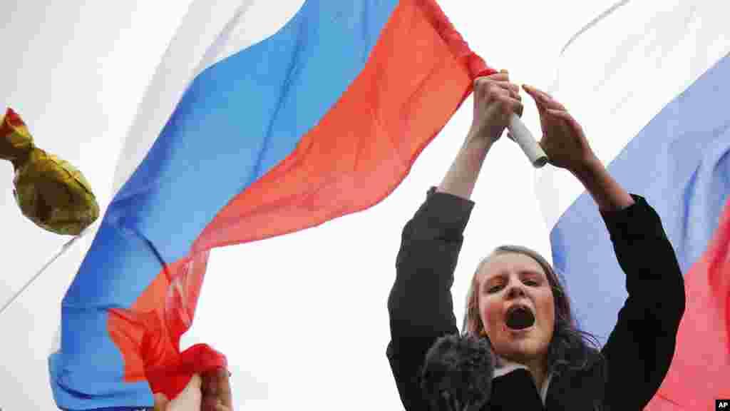 Les manifestants crient des slogans et brandissent des drapeaux russes lors d'un rassemblement à Moscou, en Russie, le 7 octobre 2017.