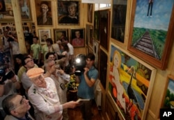 FILE - Russian poet Yegeny Yevtushenko, second left, is seen at the opening of his museum in Peredelkino, outside Moscow, July 17, 2010. Over a hundred paintings, including works by Pablo Picasso and Marc Chagall, and pictures made by the poet were on display.